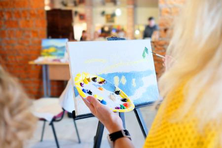 Kunstenaar die aan een schilderij werkt Stockfoto