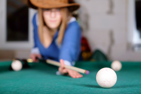 billiards hall: women are concentrated on a billiard ball number eight Stock Photo