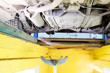 hoist: Car under repair on hoist at service station