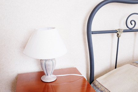 bedside lamp: Hotel room Interior. Table lamp on the bedside table Stock Photo