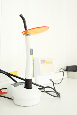 curing: Dental ultraviolet curing light tool with orange UV light blocking glass Stock Photo