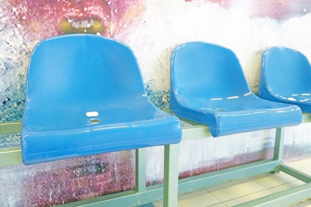 beat the competition: Blue plastic armchairs on stadium tribune in pool Stock Photo
