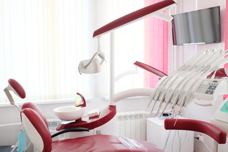 Dental clinic interior design with red chair and tools Banque d'images