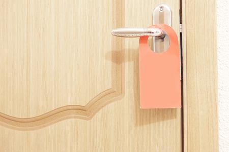 Image of a do not disturb sign hang on door knob photo