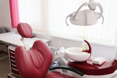 Dental clinic interior design with red chair and tools Stock Photo
