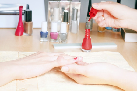 manicurist: Manicurist doing manicure client painting nails with red nail polish in salon on yellow towel