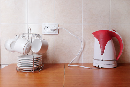 White coffee cups with saucers and electric kettle photo
