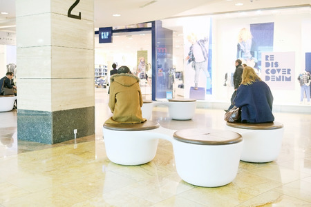 afimall: RUSSIA, MOSCOW - MARCH 19, 2015: Shopping center Afimall City people sit on chairs