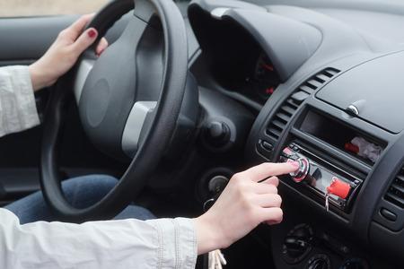 Woman adjusting radio volume in the car.