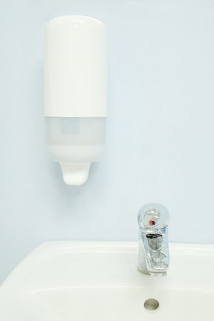 to sink: Soap dispenser above the sink