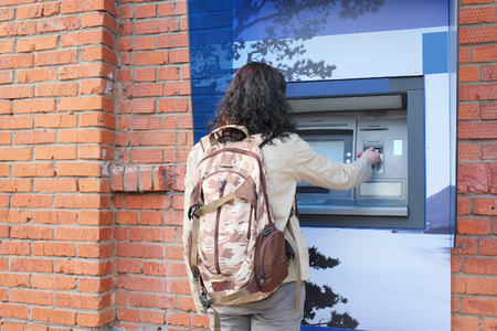 withdrawing: Woman with backpack withdrawing money from credit card at ATM.
