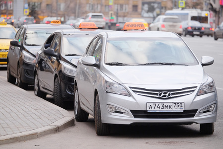 sectoring: MOSCOW, RUSSIA - APRIL 22, 2015: Taxis waits for passengers. Taxi cars on the street of Moscow Editorial