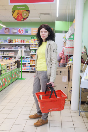 affordable: MOSCOW, RUSSIA  -  APRIL 09, 2015: Supermarket Pyaterochka with the most affordable prices. Russias largest retailer. Woman carrying red basket while shopping in the supermarket