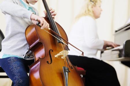violoncello: The performer plays  a violoncello during a concert