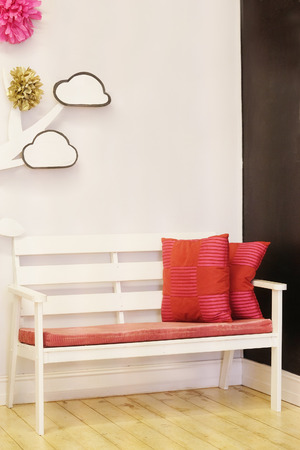 red pillows: White bench with red pillows Stock Photo
