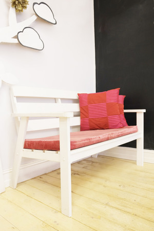 soft furnishing: White bench with red pillows Stock Photo
