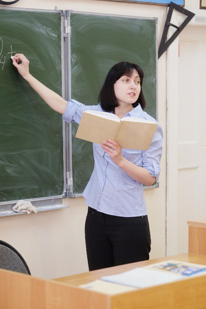 pedagogical: Teacher stands at a blackboard