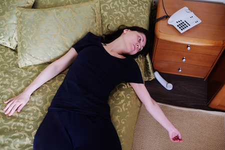 the unconscious: Girl lying unconscious next to the handset out Stock Photo