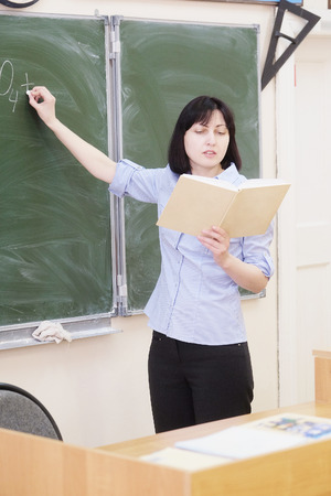 obligatory: The teacher stands at a blackboard