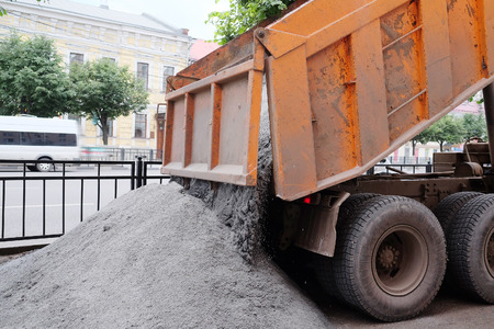 dumptruck: The dump truck pours out cement on the repaired sidewalk