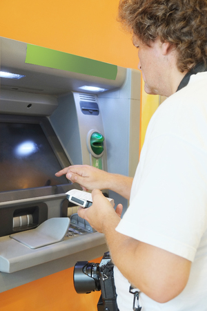 The man withdraws money from the ATM photo