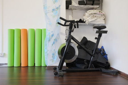 bycicle: Interior of a fitness hall with the fitness bycicle Stock Photo