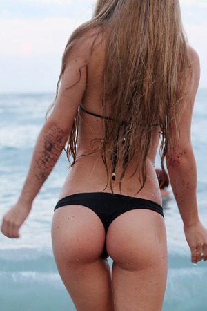 Girl on a sea beach. View from a back
