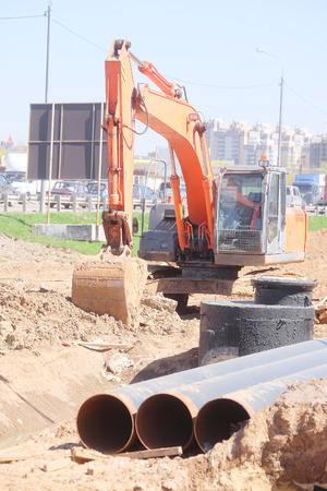 earth moving equipment: excavator works at a construction