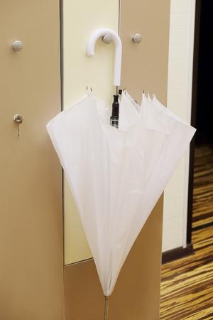 cloakroom: White umbrella on a closed doors in a cloak-room