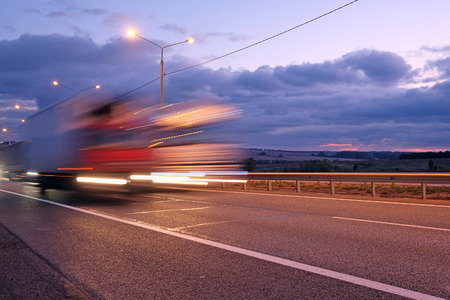 semi: Truck on a highway in the night Stock Photo