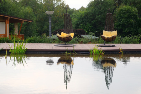 daybed: The image of chaise-longues around the pond outside