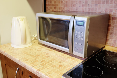 microwave oven: Electric kettle and microwave oven in the kitchen environment Stock Photo