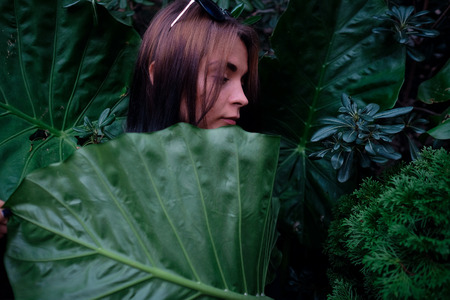 stays: Portrait of a young girl stays behind a big leaf Stock Photo