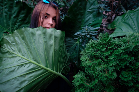 big behind: Portrait of a young girl stays behind a big leaf Stock Photo