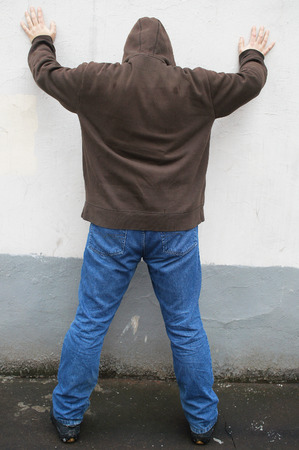 hoodlum: guy stands with his hands on a wall waiting for search incidental to the arrest