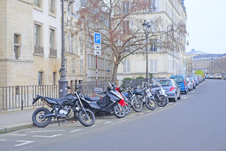 a two wheeled vehicle: Paris, France, February 9, 2016: motorcycle parking on a street in a center of Paris, France. Motorcycles are very popular transport in Paris