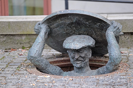 Statue of man getting out of a manhole, Stockholm, Sweden