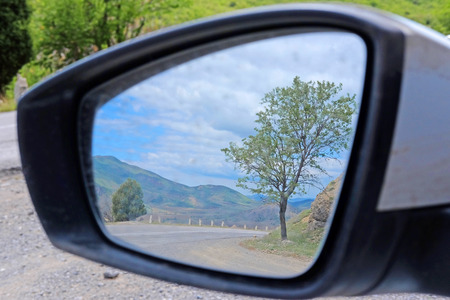 rearview: reflection of the mountain road in a car rear-view mirror