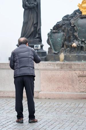 Prague, Czechia - November, 21, 2016: tourist makes photo on Charles Bridge in Prague, Czechia