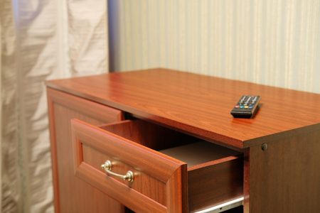 clicker: commode with an open drawer and a clicker on it in a hotel room Stock Photo
