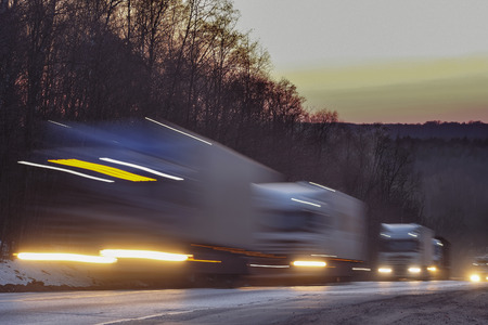light chains: Trucks on a highway in an evening Stock Photo