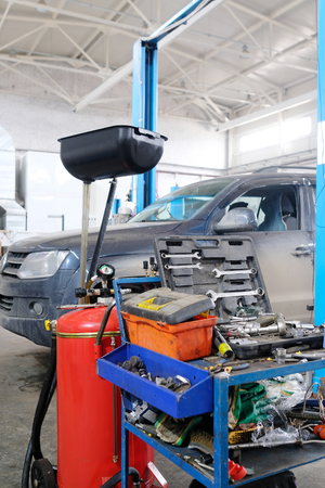 Stupino, Moscow region, Russia - April, 4, 2017: Interior of a car repair station in Stupino, Russia. There is a device for oil changing and tools trolley on the frontground Editorial
