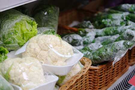 cauliflower and other vegetables on a shelf in a shop Stock Photo