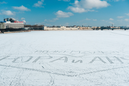 St. Petersburg, Russia - March, 7, 2017: The inscription Yura and Ania made by boots traces on ice of the frozen Neva River in St. Petersburg, Russia Редакционное