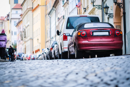 cars on a street parking in the Old town of Prague, Czechia Stock Photo
