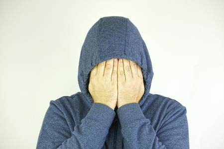 Man in a jacket with hood closes his face with the hands