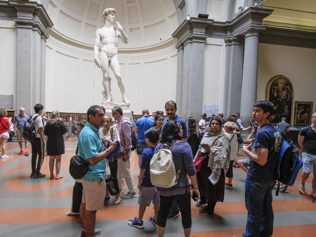 Florence, Italy - June, 3, 2018: Visitors in a museum of Florence Academy of fine arts (Accademia di belle arti di Firenze) watch the statue of David by Michelangelo