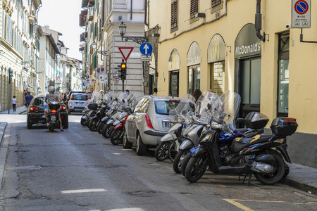 Florence, Italy - May, 4, 2018: bikes and cars on a parking in Florence