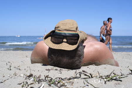 man sunbathes on the beach with a cap on the head