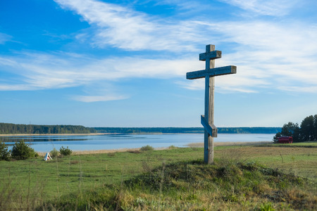 Landscape with the image of cross on a bank of lake Seliger in Russia Imagens